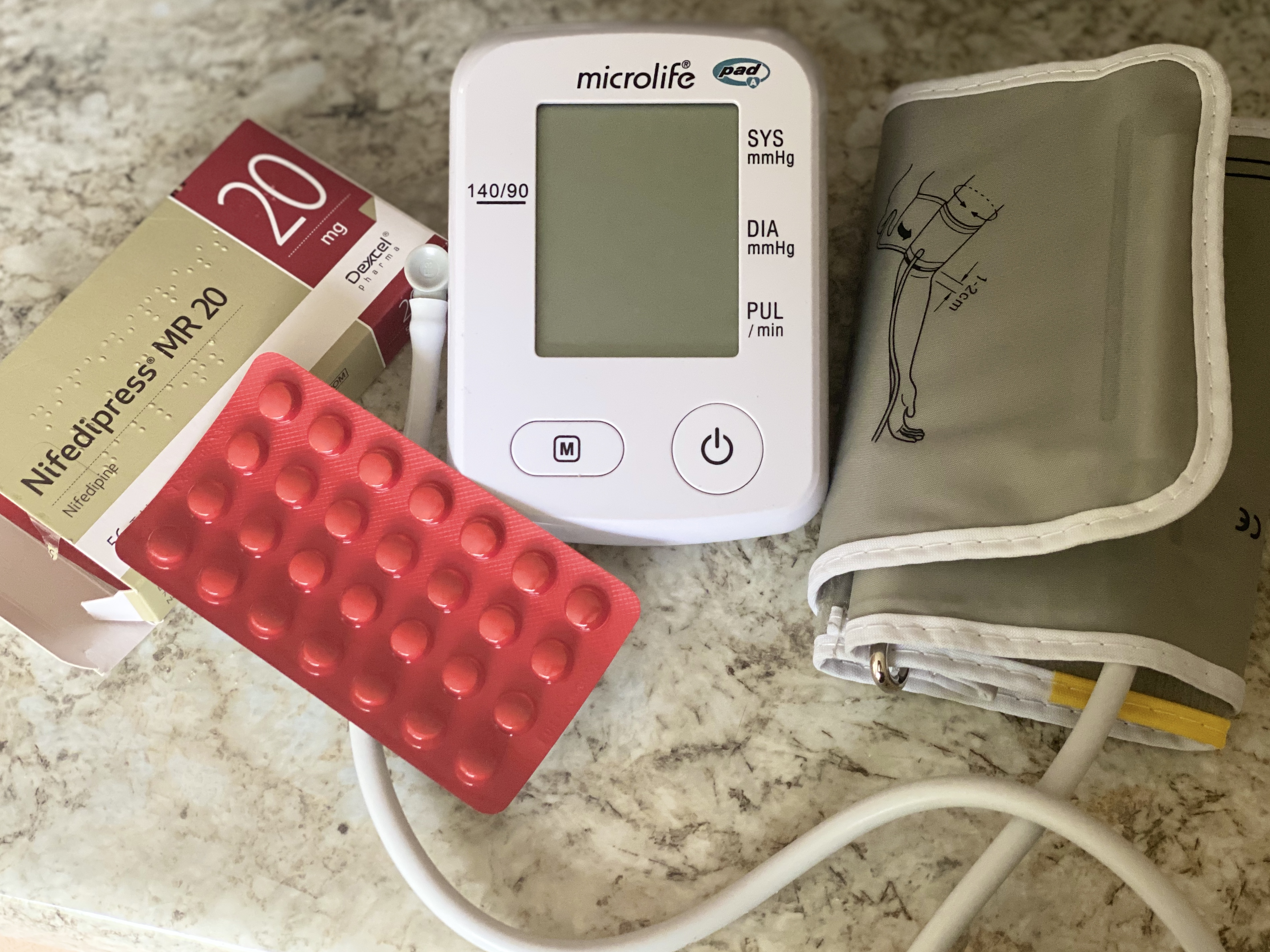 Blood pressure monitor alongside medication lying on a marble surface.